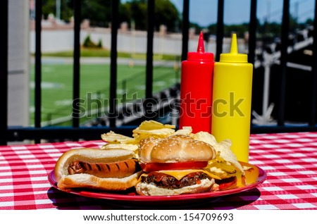 Tailgate party with cheeseburger, hot dog, potato chips and mustard and ketchup bottles.  Football field in background.
