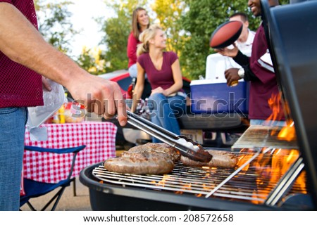 Tailgating: Bratwurst Cooking On Grill For Tailgate Party - stock photo