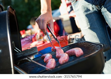 Tailgating: Man Grilling Sausages On Charcoal Grill For Party - stock photo
