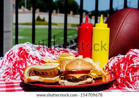 Tailgating party with cheeseburger, hot dog, potato chips, pom poms, and football.  Football field in background. - stock photo