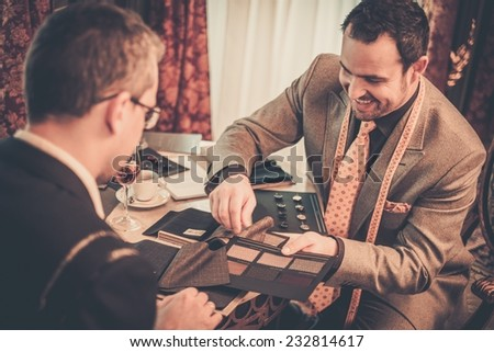 Tailor and client choosing cloth and buttons for custom made suit