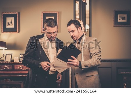 Tailor and client choosing cloth for custom made suit  - stock photo