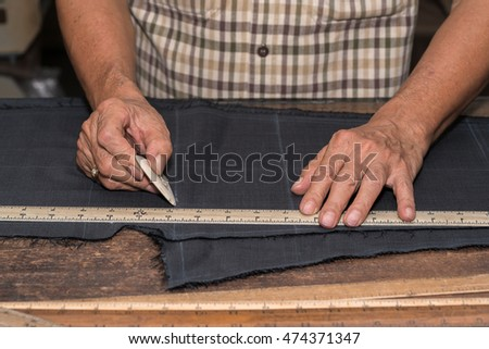 Tailor at work, drawing line on fabric with chalk