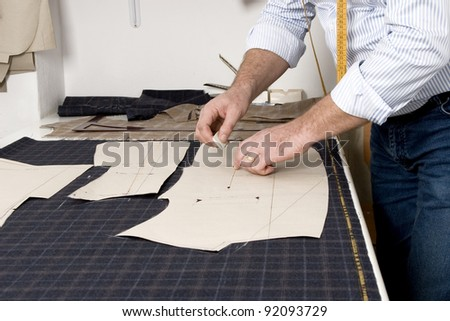 Tailor at work, drawing line on fabric with chalk - stock photo