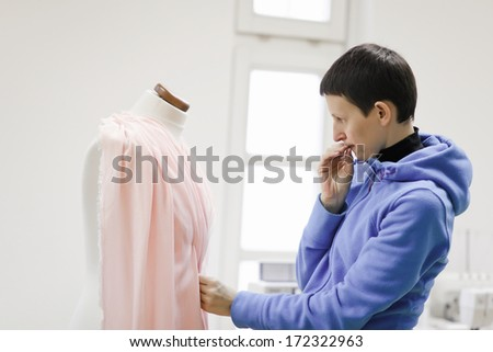 Tailor creating dress in her shop. Small business concept.