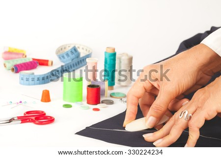 Tailor designing clothes, sewing tools in background - stock photo