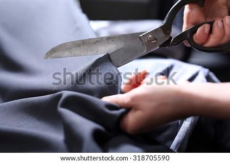 Tailor.Hands notch tailor tailor's scissors cloth. - stock photo