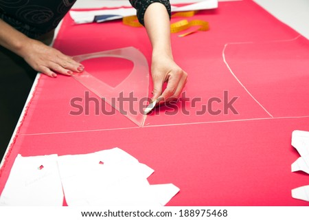 tailor hands working with pink fabric.Close up - stock photo