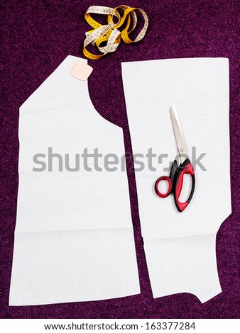 tailor instruments and pattern cut of woollen clothes on cutting table - stock photo