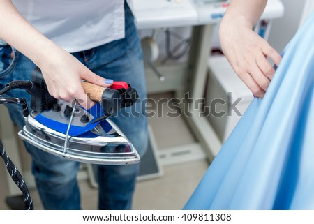 Tailor ironing the fabric. seamstress irons dress in a sewing workshop - stock photo