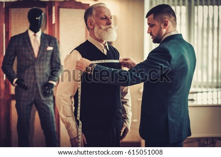 Tailor measuring client for custom made garment