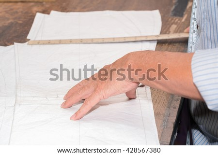 Tailor or clothing designer marking out a pattern for a handmade garment