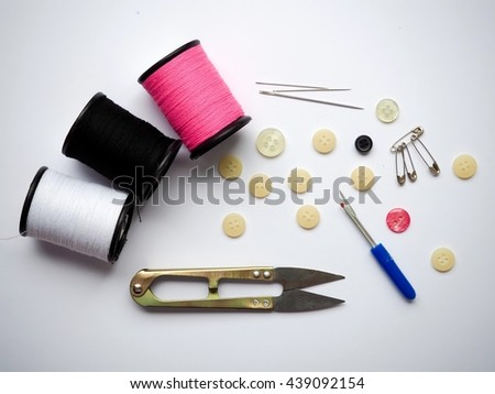 Tailor's tool on white background , concept of tailor's tool with thread , sewing needle , button , cutting board , on white background , top view  - stock photo