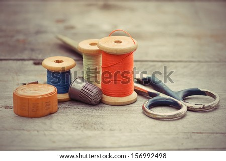 tailor's tools - the old scissors, spools of thread, tape centimeter, thimble on a wooden background - stock photo
