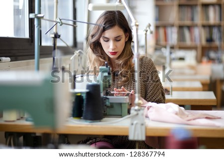 Tailor sewing in workshop - stock photo