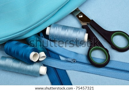 Tailor tools on blue material background - stock photo