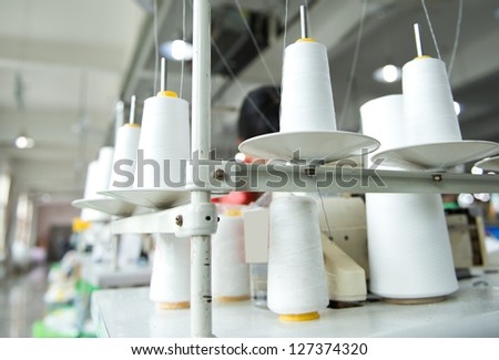Tailor using industrial sewing machine with group of cotton spools. - stock photo