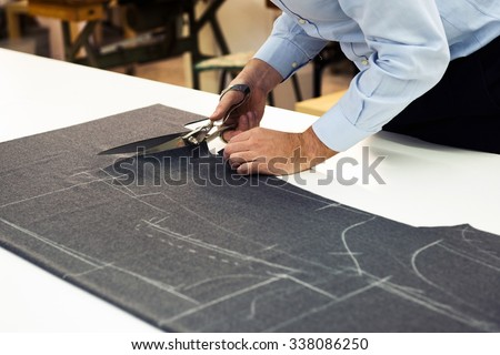 Tailor working in his shop cutting a roll of dark fabric on which he has marked out the pattern of the garment he is making with tailors chalk, close up view