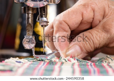 Tailor working on a sewing machine - stock photo
