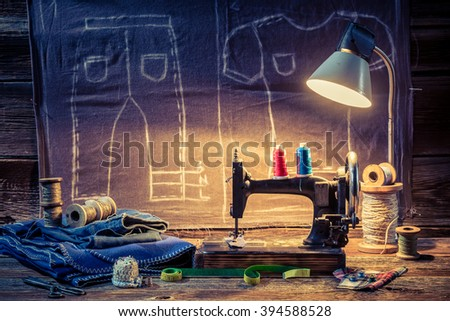 Tailor workshop with cloth, sewing machine and scissors - stock photo