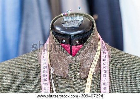 tailoring of male green tweed jacket on mannequin and ready suits on background - stock photo