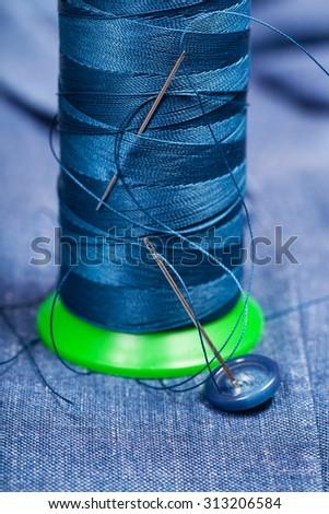 tailoring still life - thread bobbin with needles, button on blue silk textile - stock photo