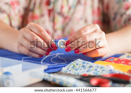 tailoring woman hands close-up with button