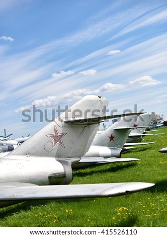Tails of the old Soviet aircraft at the airport on a background cloudy sky - stock photo