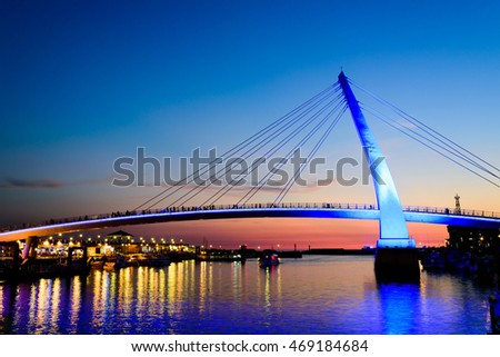 Taipei, Taiwan -  July 31, 2016:Night view of a bridge across river that glows in sunset.