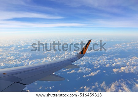 TAIPEI, TAIWAN - NOV 3: Tiger airway plane, view of airplane wing with clouds and sky  on November 3, 2016. The plane en route from taipei to Don Muang Airport in Bangkok