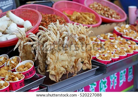 TAIPEI, TAIWAN - Oct 31: Deep sea squid fried on walking street of Tamsui Old Street The street has many kind of traditional food and snack on Octcber 31, 2016 in Taipei, Taiwan