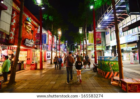 TAIPEI, TAIWAN - OCT  2013 : Locals and tourists walking at the Ximending street market in Taipei, Taiwan on October 21, 2013. This street is full of food stalls, shops, cafes, restaurants. - stock photo