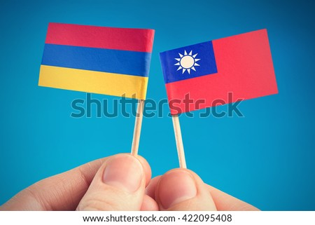 Taiwan and Armenia - flags in the hands on blue background - stock photo