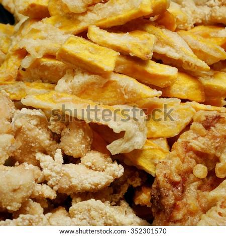 Taiwanese fried crispy sweet potato fries and deep fried popcorn chicken at food street night market. - stock photo