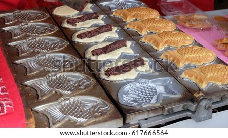 Taiyaki, a Japanese fish-shaped cake with red bean paste filling made from sweetened azuki beans, on a machine ready to be baked