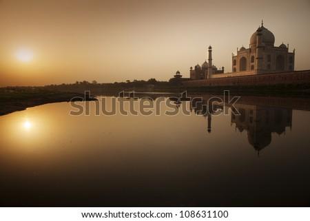 Taj Mahal at sunrise/  building silhouette reflexion in the river Yamuna - stock photo