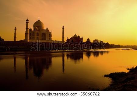 Taj Mahal at sunset reflected in the Yamuna river. - stock photo