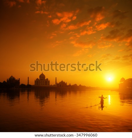 Taj Mahal in Agra, India in golden sunset with silhouette of fisherman. - stock photo