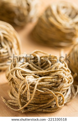 Tajarin or Tagliolini, made with fresh eggs and buckwheat flour, a specialty pasta shape from Piemonte, region of Italy - stock photo