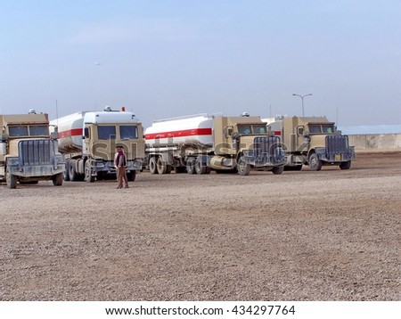 TAJI, IRAQ - CIRCA 2005: Rows of armored fuel tankers lined up from a convoy on a Forward Operating Base north of Baghdad