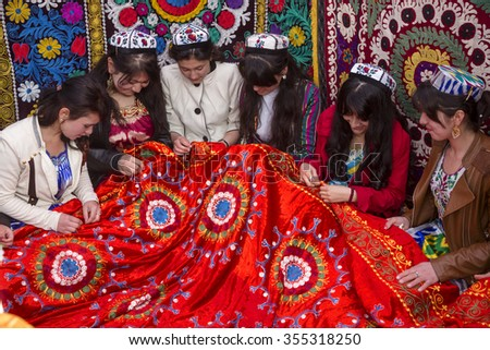 TAJIKISTAN, KHUJAND, 21 MARCH 2015: Tajik girls embroider beautiful carpet in Central Park Navruzgoh during the celebration of Nowruz (New Year) in the city of Khujand, Tajikistan Republic - stock photo