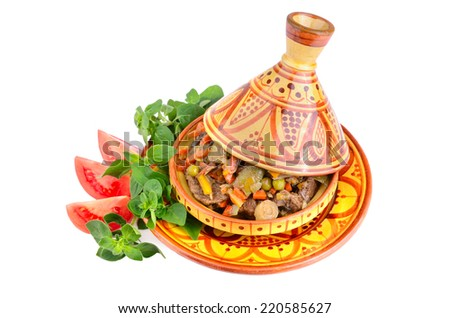 Tajine full of meat and vegetables with marjoram and tomatoes on a white background