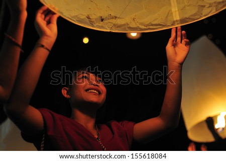 TAK THAILAND - DECEMBER 28 : Undentified girl float paper lantern in Loy Kra Tong festival of Thailand on December 28, 2012 This activity is luck for people in UMPANG, Tak, Thailand.  - stock photo