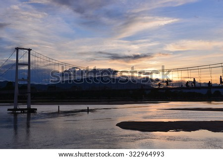 TAK,Thailand-June 18, 2015:Sunset landscape at The old wooden bridge(Mon bridge ) across the Ping river at Tak Province, Thailand