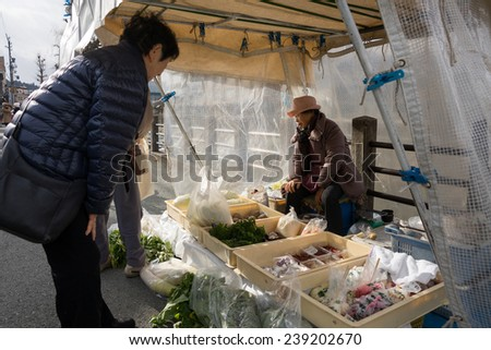 TAKAYAMA, JAPAN - DECEMBER 3, 2014: Local buys at a stall at the Miyagawa morning market in Takayama, Japan. This marketplace sells food items, groceries to farm produce and is common in rural Japan.  - stock photo