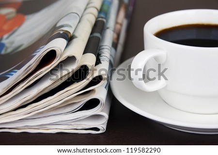 Take a break: pile of newspapers and cup of coffee on the table - stock photo