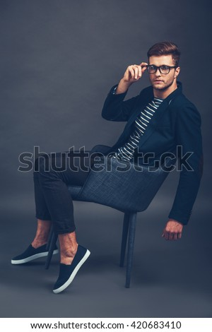 Take a closer look at my style. Confident young handsome man adjusting his glasses and looking at camera while sitting in chair against grey background - stock photo