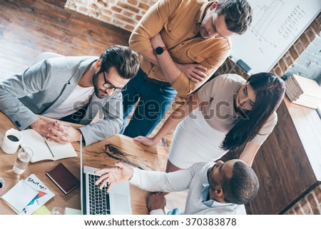 Take a look at our results! Top view of group of four young people discuss something and gesturing while leaning to the table in office - stock photo