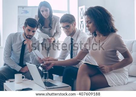 Take a look at this statistics! Young beautiful African woman pointing at her laptop while sitting on the couch at office with her coworkers - stock photo