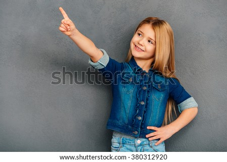 Take a look here! Cheerful littlegirl pointing away and smiling while standing against grey background - stock photo